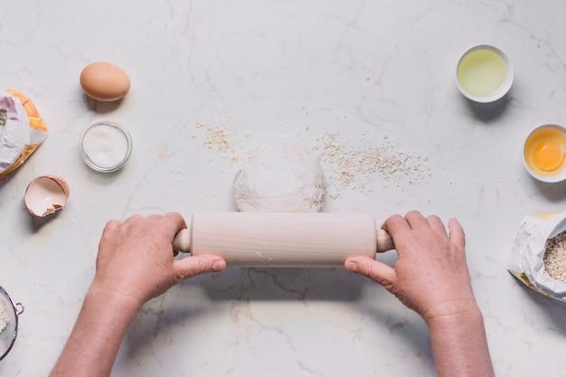 Erhöhte ansicht der hand einer person, die teig mit nudelholz platt macht