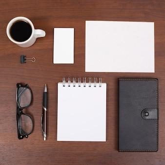 Erhöhte ansicht der kaffeetasse und des büromaterials auf hölzernem schreibtisch