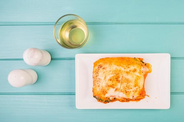 Erhöhte ansicht der köstlichen lasagne nahe salzstreuer