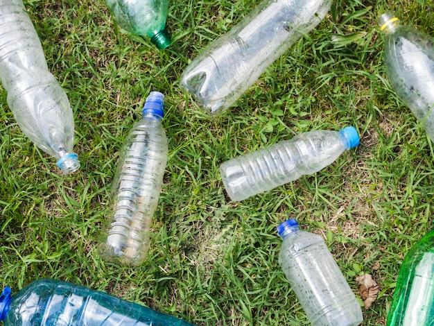 Erhöhte ansicht der leeren plastikflasche auf gras