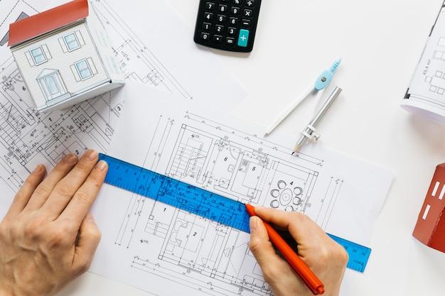 Erhöhte ansicht der menschlichen hand arbeitend an blaupause im immobilienbüro