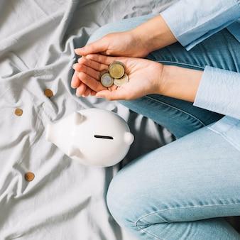 Erhöhte ansicht der menschlichen hand mit münzen nahe piggybank