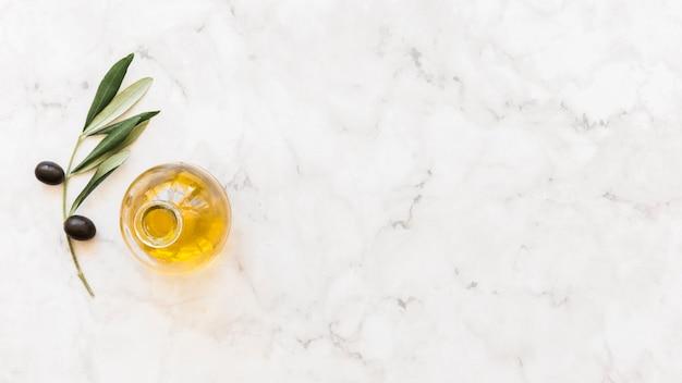 Erhöhte ansicht der olivenölflasche mit dem zweig auf marmorhintergrund