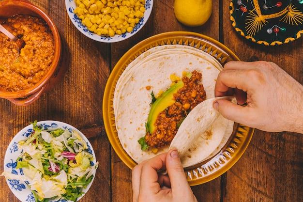 Erhöhte ansicht der personenhand, die verpackungsrindfleisch tacos zum frühstück zubereitet