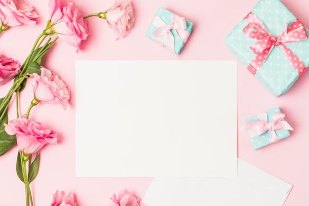 Erhöhte ansicht der rosa blume; weißes leeres papier und dekorative geschenkbox