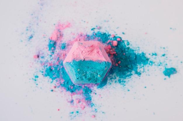 Erhöhte ansicht der rosa und blauen farbigen badebombe auf weißem hintergrund
