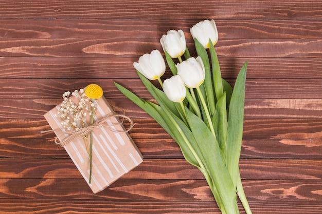 Erhöhte ansicht der weißen tulpe blüht mit geschenkbox über hölzernem strukturiertem hintergrund