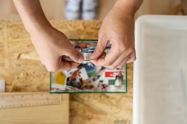 Erhöhte ansicht der zerreißenden papierhand einer frau über glasbehälter