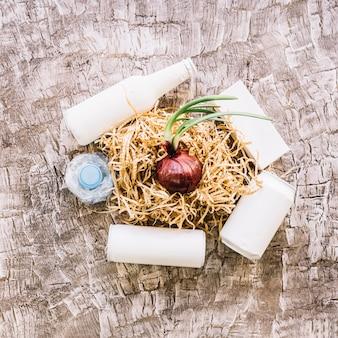 Erhöhte ansicht der zwiebel mit woodshave umgeben durch klare weiße flaschen