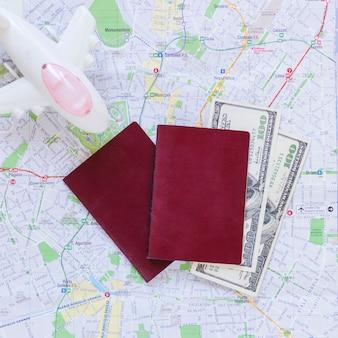 Erhöhte ansicht des flugzeugs; reisepass; banknoten und karte