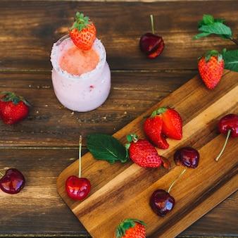 Erhöhte ansicht des frischen smoothie nahe kirschen und der erdbeeren auf schneidebrett