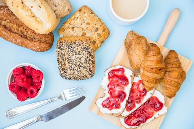 Erhöhte ansicht des gebackenen lebensmittels mit erdbeeren und tee auf blauem hintergrund