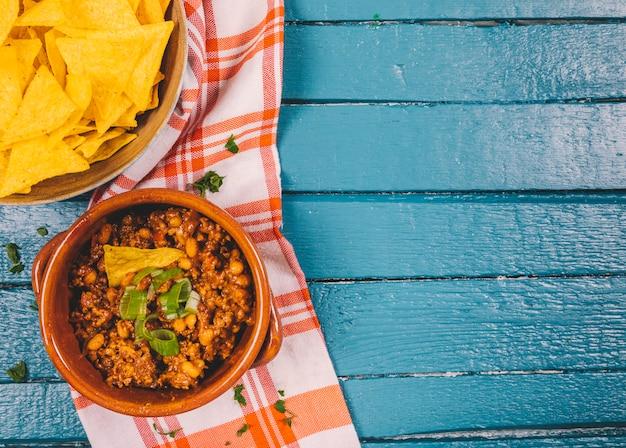 Erhöhte ansicht des gekochten rinderhackfleischs in der schüssel mit mexikanischen nachochips auf blauem hölzernem schreibtisch