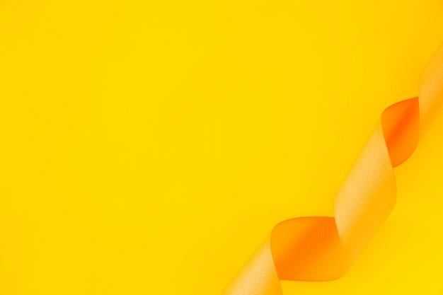 Erhöhte ansicht des gekräuselten satinbandes auf gelbem hintergrund