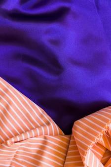 Erhöhte ansicht des geraden mustertextils auf glattem blauem gewebe