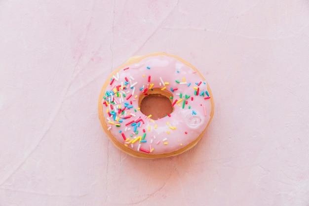 Erhöhte ansicht des geschmackvollen donuts mit besprühen lokalisiert auf rosa hintergrund