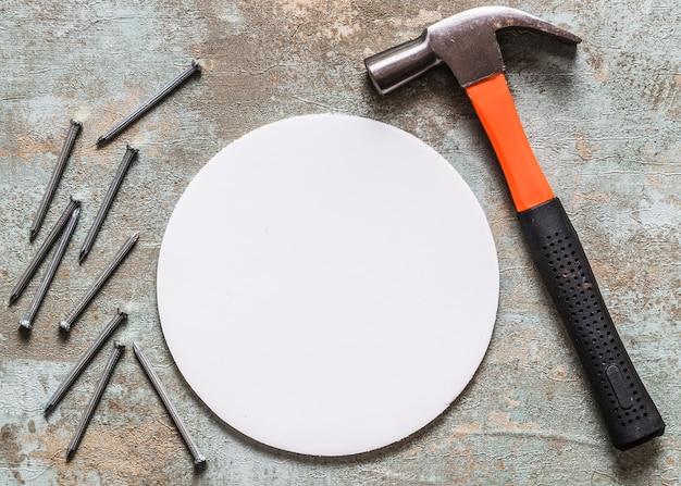 Erhöhte ansicht des hammers, des kreisrahmens und der nägel auf rostigem hintergrund