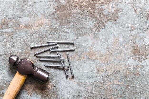 Erhöhte ansicht des hammers und der nägel auf altem hölzernem schreibtisch