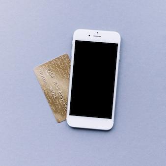 Erhöhte ansicht des handys und der kreditkarte auf grauem hintergrund