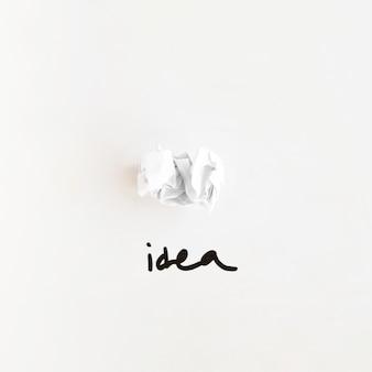 Erhöhte ansicht des ideenwortes nahe zerknittertem papier auf weißem hintergrund