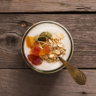 Erhöhte ansicht des joghurts mit muesli, kürbiskernen und früchten auf rustikalem holztisch