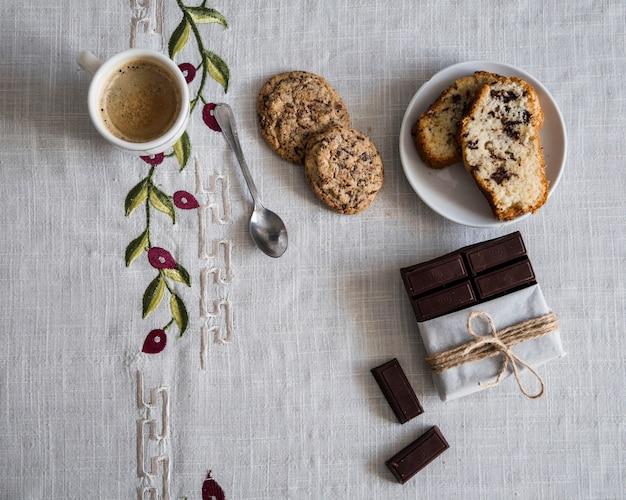 Erhöhte ansicht des kaffees mit plätzchen, brot und schokolade