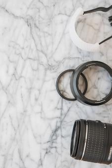 Erhöhte ansicht des kameraobjektivs und des zubehörs auf strukturiertem hintergrund des marmors