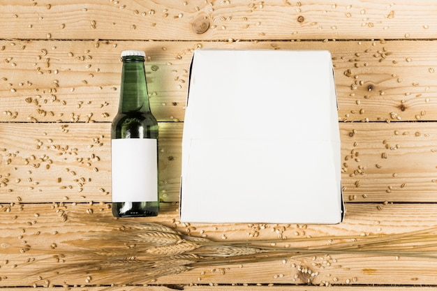 Erhöhte ansicht des kartonkastens; bierflasche und ähren auf hölzernen hintergrund