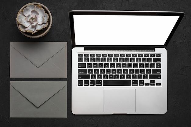 Erhöhte ansicht des laptops; umschlag und saftige pflanze auf schwarzer oberfläche