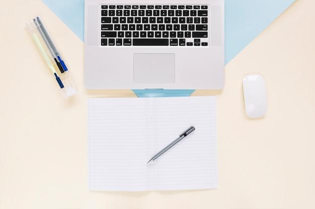 Erhöhte ansicht des laptops und der schreibwaren auf buntem papierhintergrund