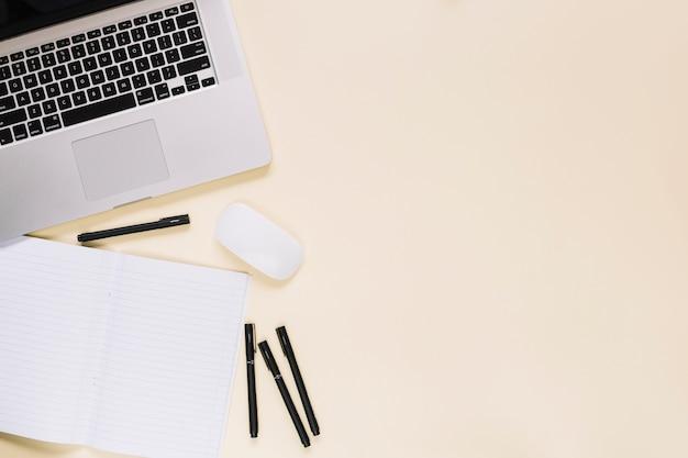 Erhöhte ansicht des laptops und des notizbuches auf sahnehintergrund