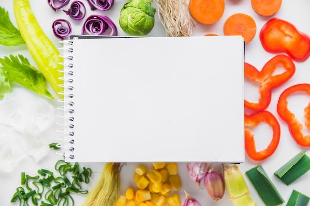 Erhöhte ansicht des leeren gewundenen notizblockes über frischem gesundem gemüse