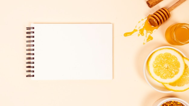 Erhöhte ansicht des leeren notizblockes mit zitronenscheibe und -honig