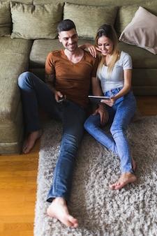 Erhöhte ansicht des mannes sitzend mit der freundin, die digitale tablette betrachtet