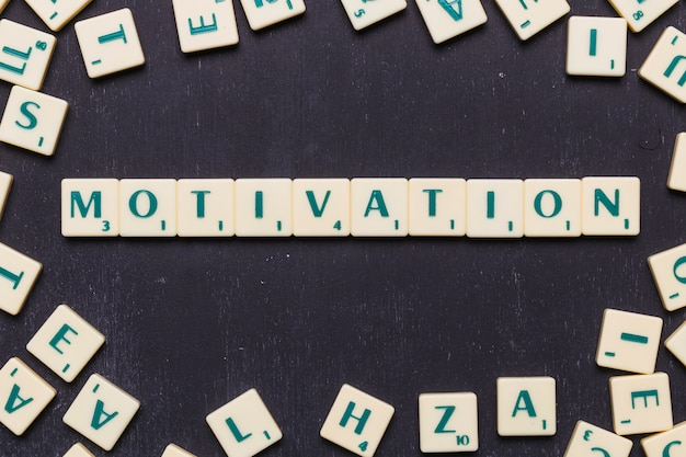 Erhöhte ansicht des motivationswortes, das vom spiel gemacht wird, scrabble buchstaben