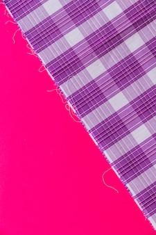 Erhöhte ansicht des purpurroten karierten mustergewebes auf rosa hintergrund