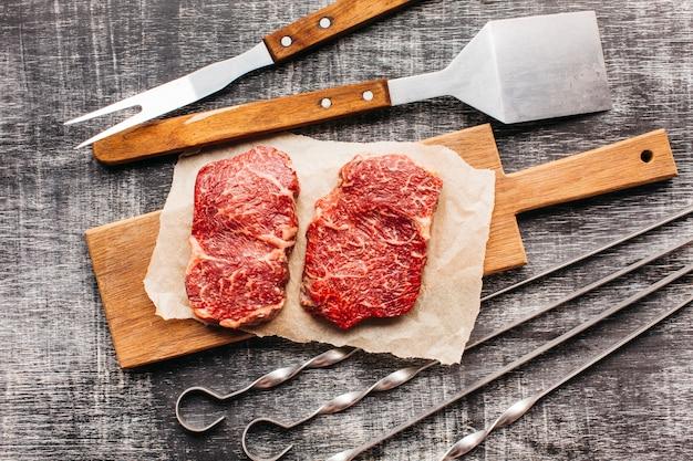 Erhöhte ansicht des rohen steaks und des grillgeräts auf hölzerner strukturierter oberfläche
