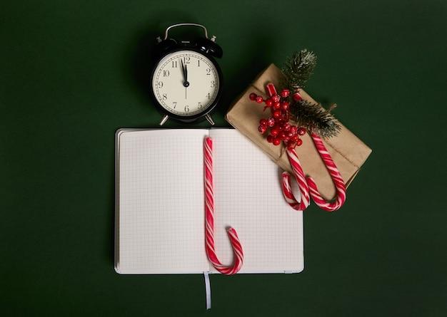 Erhöhte ansicht des weckers mit mitternacht, weihnachtsgeschenk verpackt in geschenkpapier, stechpalme, zuckerstangen und notizblock mit geöffneten seiten und leeren weißen blättern mit kopien-werbefläche