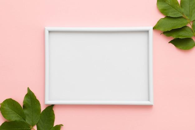 Erhöhte ansicht des weißen bilderrahmens und der grünblätter auf rosa hintergrund