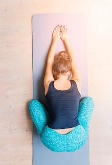 Erhöhte ansicht einer frau, die training auf yogamatte tut