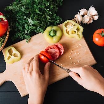 Erhöhte ansicht einer menschlichen hand, die frische rote tomate auf hölzernem hackendem brett schneidet