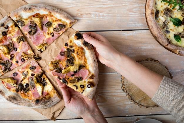 Erhöhte ansicht einer menschlichen hand, die scheibe der pizza vom braunen papier über holztisch nimmt