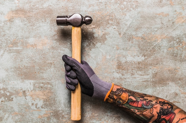 Erhöhte ansicht eines mannes, der hammer auf hölzernem schreibtisch hält