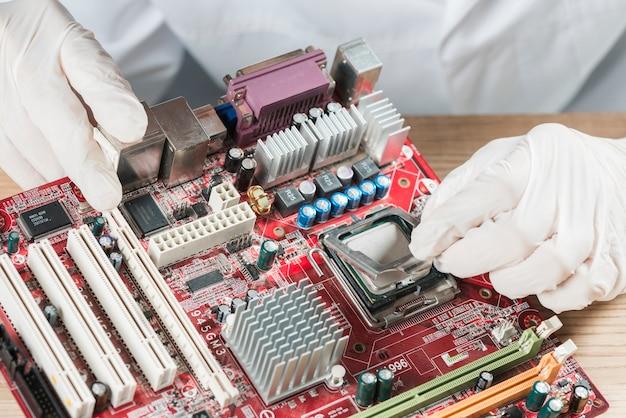 Erhöhte ansicht eines technikers, der an computermotherboard arbeitet
