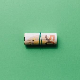 Erhöhte ansicht von aufgerollt fünfzig-euro-schein auf grünem hintergrund