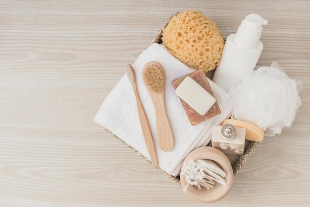 Erhöhte ansicht von badekurortprodukten mit bürsten und luffa im behälter auf holzoberfläche