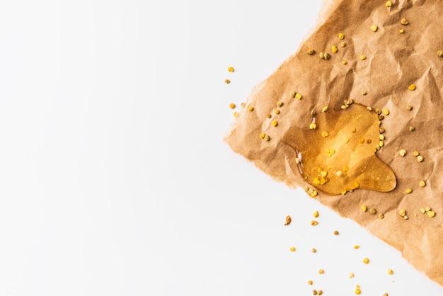 Erhöhte ansicht von bienenblütenstaubkernen und -honig auf zerknittertem braunem papier