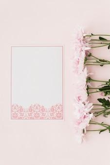 Erhöhte ansicht von blumen und von entworfenem weißbuch auf rosa hintergrund