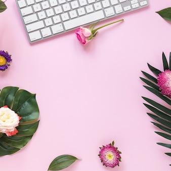 Erhöhte ansicht von blumen und von tastatur auf rosa hintergrund