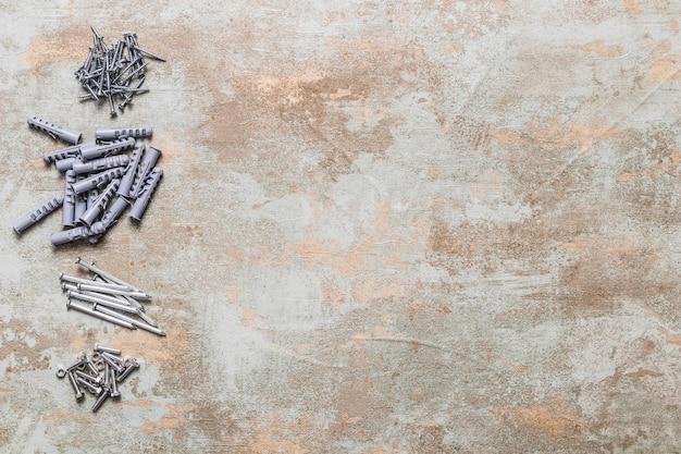 Erhöhte ansicht von bolzen, von nägeln und von wandsteckern auf altem hölzernem hintergrund
